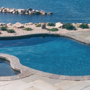 this pool and spa combination was a lot of fun as we were able to create a design that mimicked the natural shape and color of the larger body of water at